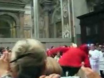 Сюзанна Майоло (в красном) пытается добраться до Бенедикта XVI. Кадр видеозаписи, переданный BBC News